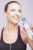 Portrait of Sporty fit woman drinking water, isolated against gr Stock Image