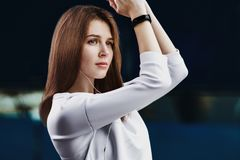 Portrait of sporty girl in white shirt performs warming-up before jogging. Stock Photo
