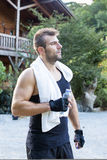 Portrait of sporty man with towels and bottle of water. Royalty Free Stock Photography