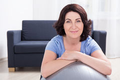 Portrait of sporty mature woman with fitness ball at home Royalty Free Stock Photos