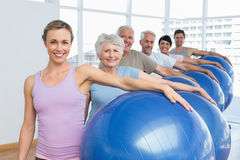 Portrait of sporty people carrying exercise balls in gym Royalty Free Stock Photos