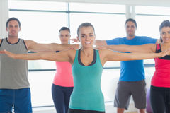 Portrait of sporty people stretching out hands at yoga class Stock Photography