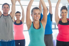 Portrait of sporty people stretching up hands at yoga class Stock Images