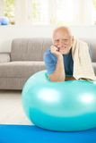 Portrait of sporty senior man with exercise ball. Looking at camera, smiling Stock Image