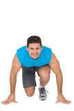 Portrait of a sporty smiling man in running stance Royalty Free Stock Photography