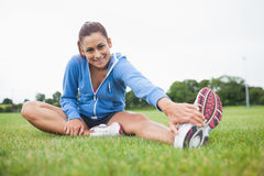 Portrait of a sporty stretching her leg on the grass Royalty Free Stock Images