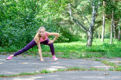 Portrait of sporty woman doing stretching exercises in park before training. Female athlete preparing for jogging royalty free stock photos