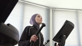 Portrait of a sporty woman in hijab on a step simulator, fitness muslim. Close up stock video