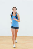 Portrait of a sporty woman in jogging posture at fitness center Royalty Free Stock Photography