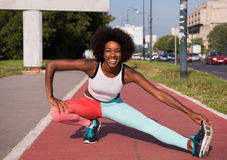 Portrait of sporty young african american woman stretching outdo Stock Photo
