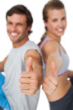 Portrait of a sporty young couple gesturing thumbs up Royalty Free Stock Photo