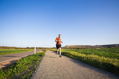 Portrait of a sporty young man running outdoors in nature Royalty Free Stock Photo
