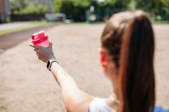 Portrait of a sporty young woman with a bottle of cool water on the summer sports field from the back. Healthy lifestyle stock images