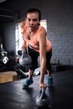 Portrait of sporty young woman holding kettlebell Royalty Free Stock Images