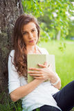 Portrait of spring brunette girl seating outdoor at the tree wit Stock Photos