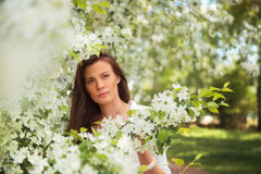 Portrait of spring brunette girl standing outdoor in blooming tr Royalty Free Stock Photography