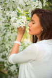 Portrait of spring brunette girl standing outdoor in blooming tr Royalty Free Stock Images