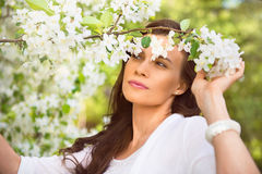 Portrait of spring brunette girl standing outdoor in blooming tr Stock Photo