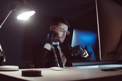 Portrait of spy agent in gloves with headset checking time at table with computer screen. In dark stock photo