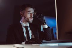 Portrait of spy agent with headset looking at computer screen at table. In dark royalty free stock photography