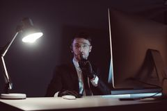 Portrait of spy agent showing silence sign at table with computer screen. In dark royalty free stock photo