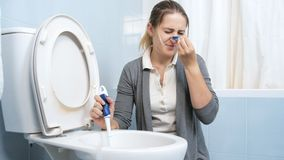 Portrait of squeamish young woman putting clothespin on her nose before washing toilet. Portrait of squeamish woman putting clothespin on her nose before washing stock images