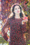 Portrait of standing autumn girl in fall head wreath with red apple in hand Stock Photography
