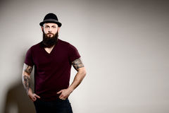 Portrait of standing handsome bearded man in hat. Gray background Stock Images
