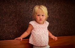 Portrait of standing little blonde girl in pink against brown wall Stock Photography