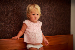 Portrait of standing little blonde girl in pink against brown wall Stock Photo