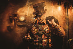 Portrait of steampunk man with various mechanical devices on vintage steampunk background Stock Photos