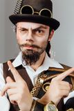 Portrait of steampunk vintage man with various mechanical devices on body. stock photo