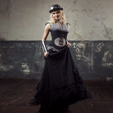 Portrait of a steampunk woman over grunge background. Beautiful lady in a Victorian style Stock Photo