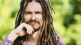 Portrait of stern man with dreadlocks. On a green background Royalty Free Stock Photo