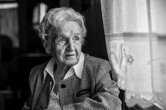 Portrait of stern old women near the window. Royalty Free Stock Image