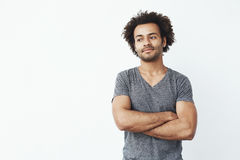 Portrait of stong and handsome african man looking left posing with crossed arms over white wall. Confident startup. Portrait of stong and handsome african man Stock Photo