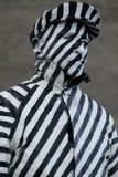 Portrait of a street artist. A street artist painted with black and white stripes standing still Stock Photos