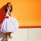Portrait street fashion little girl in dress. Near colorful wall Royalty Free Stock Photo