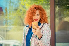 Frustrated woman holding cellphone in hand on the city street in royalty free stock images