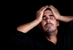 Portrait of a stressed and sad young man. With a dramatic expression on a black background Stock Image