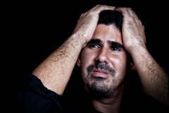 Portrait of a stressed and sad young man. With a dramatic expression on a black background Stock Images