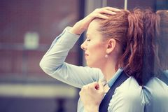 Portrait stressed sad young woman outdoors. Urban life style stress. Closeup side view profile portrait stressed sad young woman outdoors. City urban life style