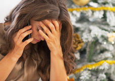 Portrait of stressed woman in front of christmas tree Royalty Free Stock Photos