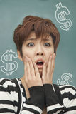 Portrait of stressed young woman with money problems, in front of blackboard with money signs Stock Image