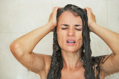 Portrait of stressed young woman in shower Royalty Free Stock Images