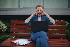 Portrait of stressful businesswoman screaming. She Holds his head with his hands.  Stock Photos