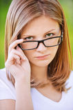 Portrait of strict woman looking. Close-up portrait of young beautiful strict blonde woman looking above her eyeglasses at summer green park Royalty Free Stock Photos