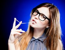Portrait of strict young woman with nerd glasses and chewing gum. Portrait of strict young woman with large nerd glasses and chewing gum royalty free stock photo