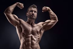 Portrait of strong Athletic Fitness man. Showing big muscles over black background royalty free stock images