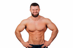 Portrait of a strong bearded male fitness model, torso. White background, isolate. hands on his hips. Very emotionally smiling eyes screwed up Stock Photos